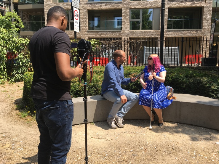 a man points a camera on a tripod at a man and a woman. They are sitting on a bench in a garden. The man holds a microphone, and the woman is speaking. She has purple hair, a blue dress and holds a white cane.