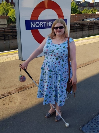 Amy standing in front of a tube sign on a platform. Holding her long white cane, she is wearing a turquoise fifties style dress with an owl print.