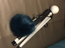 My cane folded with a dark blue fluffy pom pom