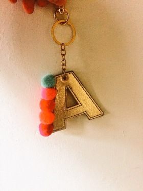 A letter A in gold fabric with pom poms down one side of the A, it's on a key chain.