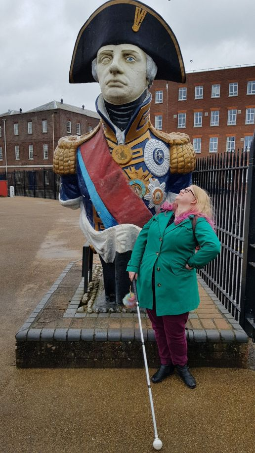 Me, standing in front of a large colourful bust of Admiral Lord Nelson, with his one eye visible. I'm wearing a green coat, burgundy trousers, and I have pink tips to my hair. I'm holding my long cane out in front of me.