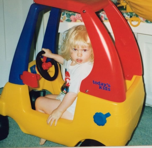 A small blonde girl is sat in a toy pedal car. The car is yellow, red and blue. Her had is on the wheel and she is facing out at the camera with a surprised expression.