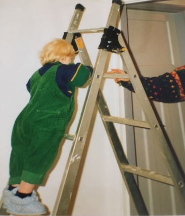 Me as a small toddler. I'm climbing a step ladder by myself. I'm about 2 years old and wearing green dungarees.
