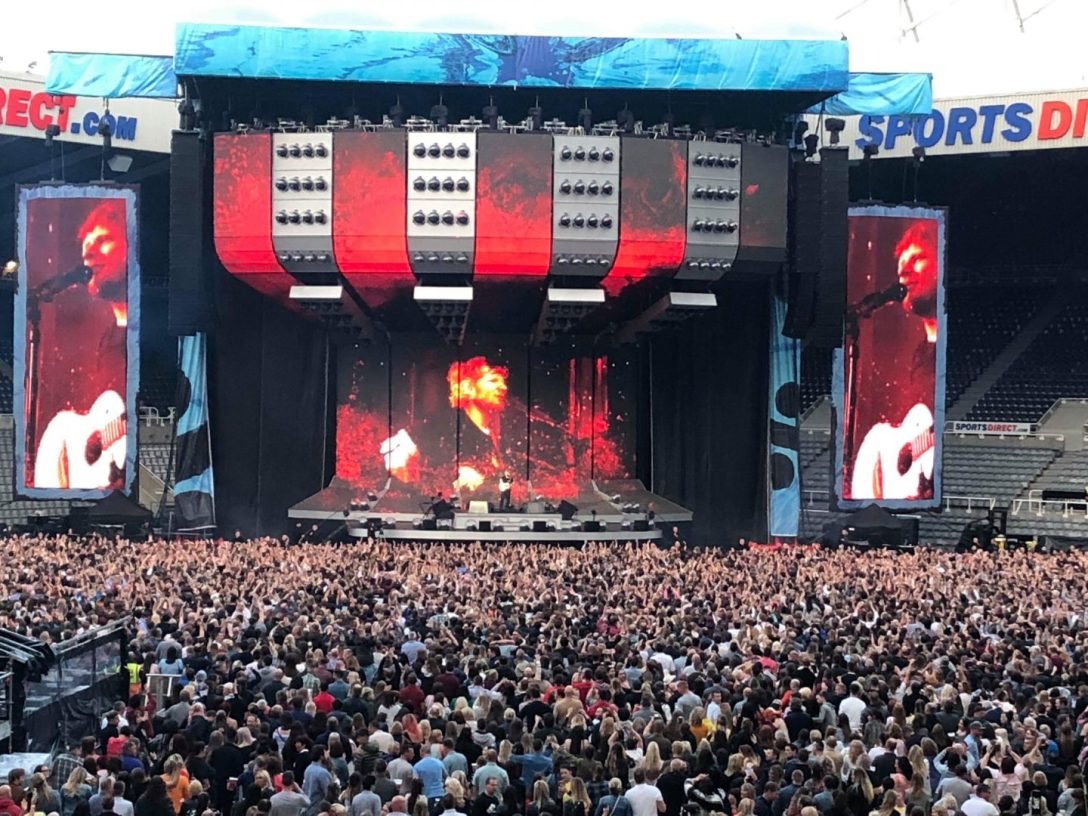 Photo of a concert. Large crowd of people. There is a stage with red lights and huge screens. Ed Sheeran is visible in the huge screens singing.