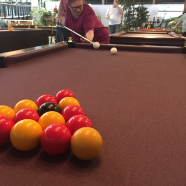 A pool table. In the foreground the red, yellow, and black balls are arranged in a triangle. On the left side, Amy can be seen posing as if about to play, she is using her long white cane as if it's pool cue. She has a concentrating face.