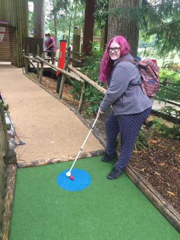 Amy is stood on a mini golf course, posing with her long white cane like a golf club. She is smiling, wearing a back pack, and posing as if she's about to hit the red gold ball with the roller ball tip of her long white cane.