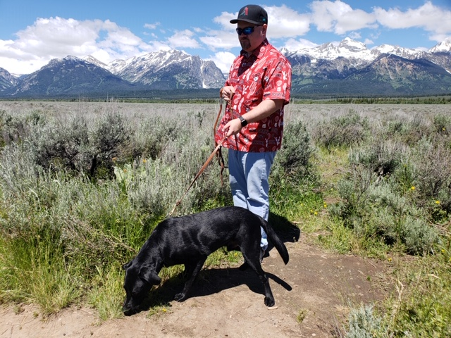 Justin, a man in a red shirt, sun glasses and baseball cap is stood holding on to his dog's lead. Behind Justin is a mountain view, and he is standing on a patch of ground surrounded by shrubs. PJ, the seeing eye dog, is a black lab, sniffing the ground excitedly.
