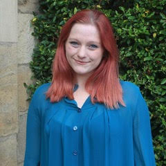 A smiling lady with red hair and a blue shirt.