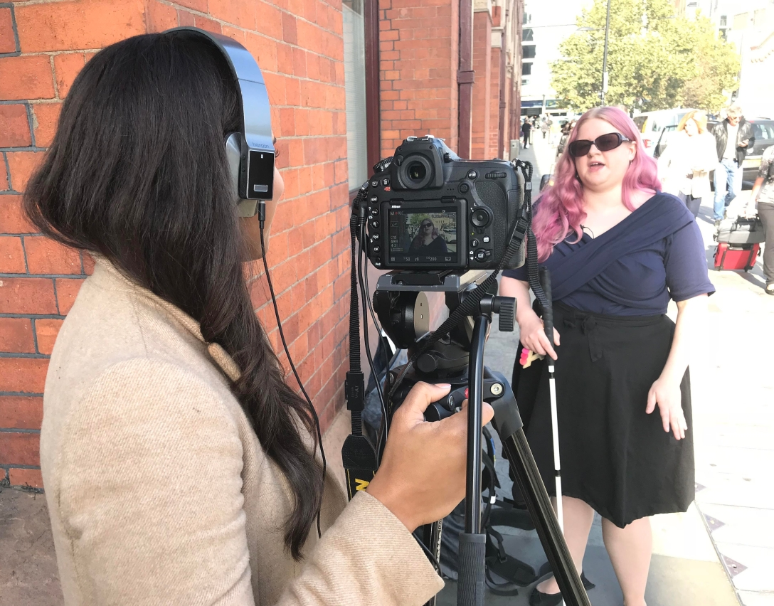 Amy is being filmed. She is standing talking and gesturing with her hands. She holds a white cane, and has dark sunglasses. A woman is filming her, viewed from behind, she wears headphones and holds the camera. The small image of Amy being filmed is visible on the camera.