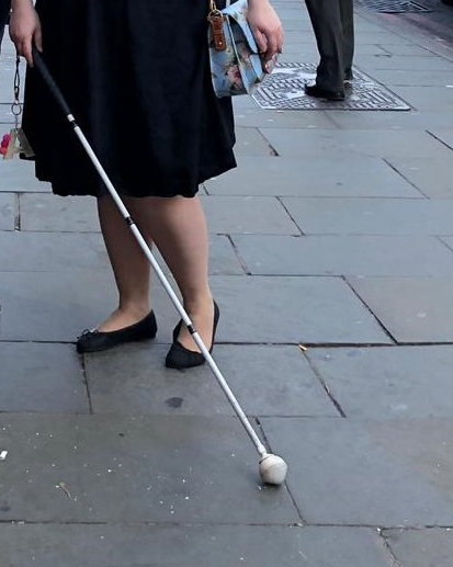 Amy's legs stood on a pavement. I'm wearing a black skirt and black pumps. I'm holding a long white cane across my body.