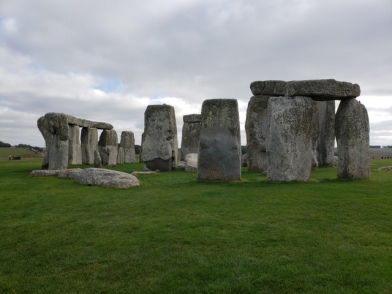 Stonehenge. A light cloudy sky with peeks of blue coming through, the large monolith stones