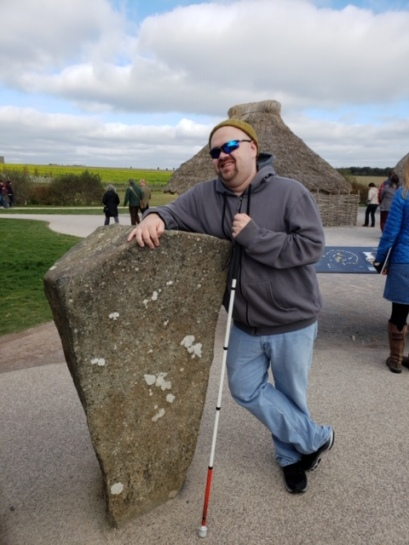 Justin leaning on an old stone, it's covered with white lichen. He wears jeans and sunglasses, leaning on the stone he smiles at the camera. Justin holds an american long white cane with the final segment in red.