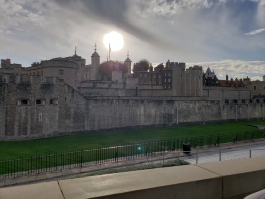 An atmospheric photo of the tower of london. The complex of the palace is grey and shadowy, with different buildings, towers, turrets and spires rising above the thick wall. A watery pale winter sun hovers above the towers with thin veils of grey and white cloud misting over the blue skies. The photos is taken from a distance, with a low wall visible in the foreground.