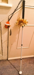 A long cane rests against a staircase cupboard. It has tinsel around the handle and a robin with a christmas hat decoration hanging from the handle.