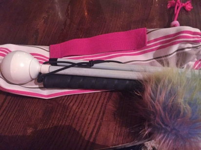 A white cane on a table. It's resting on a slender fabric case. The case is pink and stripey with a bright pink handle. The cane is folded and a rainbow coloured pom pom is resting on the handle.