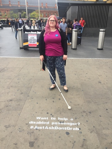 A street scene, Amy with faded pink hair stands on a pavement. She holds her long cane in front of her, she is wearing a pink tshirt. In front of her a chalk street message reads Want to help a disabled passenger, #JustAskDontGrab