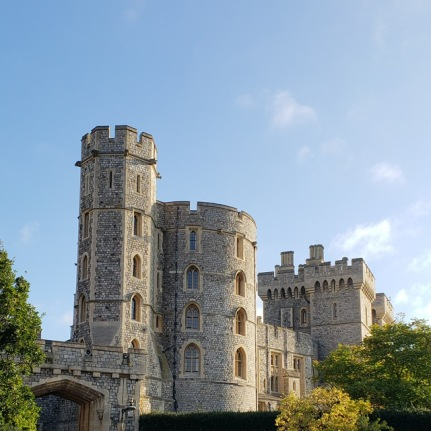 Towers at Windsor Castle. The round crenelated turrets reach into the sky, with a round tower, and square building behind them. It's a sunny day with a blue sky