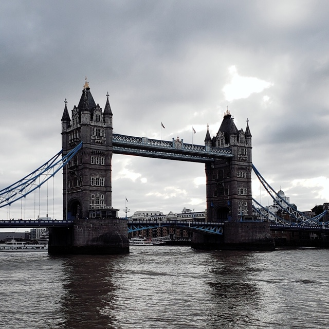 London Bridge, a grey atmospheric cloudy sky with sun breaking through.