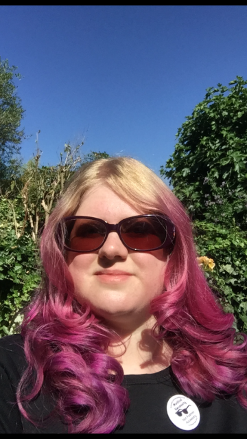 A selfie, it's a sunny day, trees and blue sky in the background. Amy is smiling looking at the camera in large round sunglasses. Her hair is blond with bright pink hair fading from the top. She is wearing a black t-shirt and badge, the badge shows a pair of sunglasses and reads, medical necessity not fashion accessory.