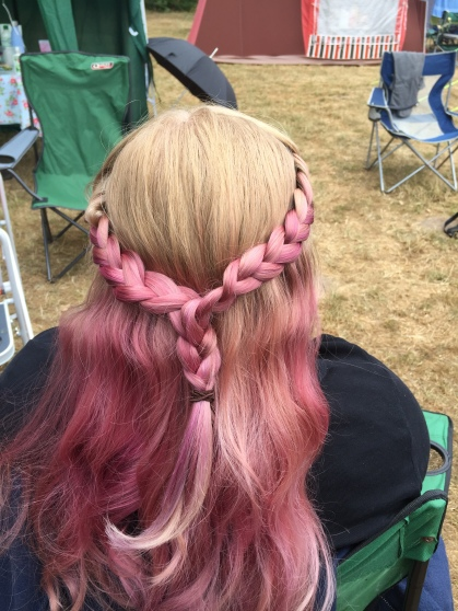 Amy's hair is braided in a french style plait. Photo is taken from the back, the plait is interwoven with fading pinks, and the rest of the hair beneath is fading from light pink and purple to rose gold. In the background a campsite.