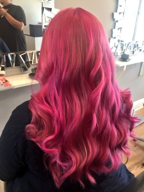 At the hairdressers. Taken from behind at an angle, Amy sits in the salon chair, mirrors in the background. Her entire hair is bright hot pink, there are waves of different pinks and purples throughout her hair. It's bright!