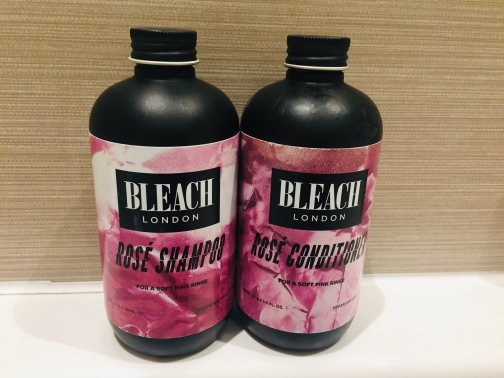 Two black bottles with pink labels. They are on the white bath top against a brown stripey tile. The labels read Bleach London, Rose Shampoo and Rose Conditioner