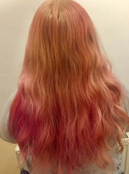 Amy's hair taken from behind, it's a soft rose pink all over, with hints of stronger pinks and purples. It is classic millenial pink!