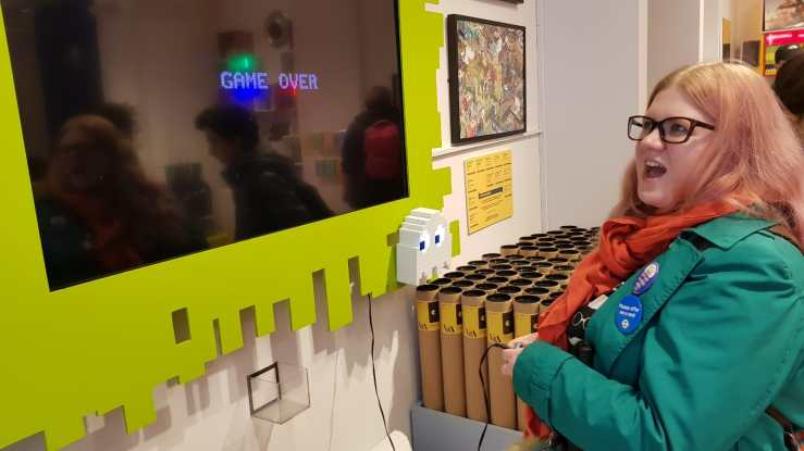 Amy stands in front of a large screen, it has a bright yellow frame, which has an uneven rectangular edge and a pacman character in the corner. Amy is looking open mouthed at the screen which displays, game over. She is holding a small controller which has a wire connecting to the screen.