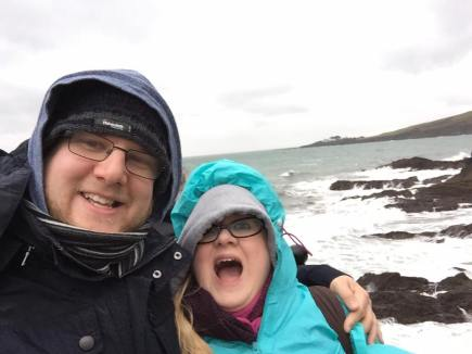 Amy and Other half stand in front of a winter sea. They both wear hoods, hats and scarves. Other Half smiles & amy has an open mouthed shocked expression.
