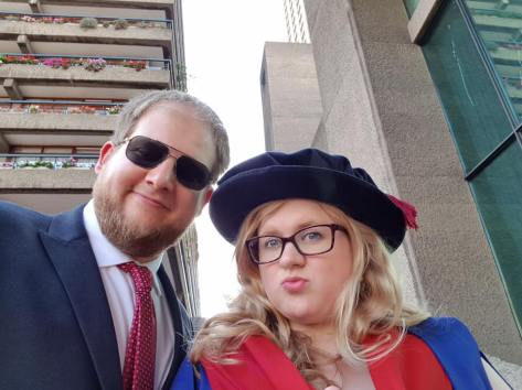 Amy's PhD graduation. Amy wears a red and blue gown, and a floppy hat with a tassle. Other Half, with a fullsome beard and aviators stands next to her in a suit and tie. Behind them the brutalist concrete architecture of the Barbican Centre in London. Amy is pouting, Other half is smiling.