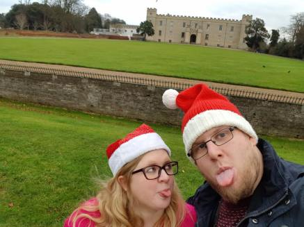Amy and Other Half stand in a country park, on a lawn, behind them a country house and another lawn. They both wear Christmas santa hats. Amy is looking at Other half with her tongue stuck out, Other half looks at the camera with his tongue stuck out.
