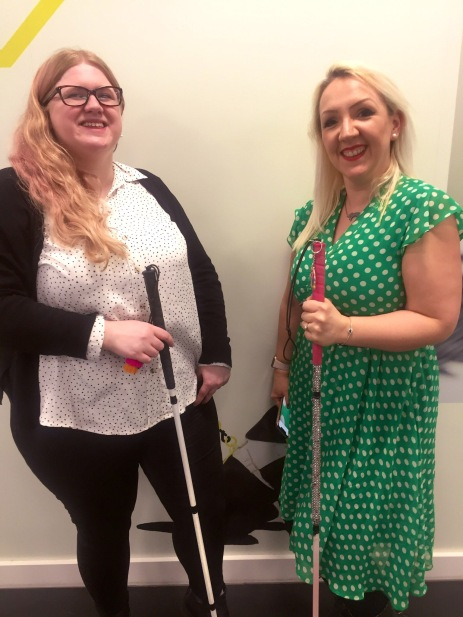 Amy and Lizzie stand next to each other. They both hold their long canes. They are smiling, Amy on the left is looking up wears glasses, a white and black spotty top and black jeans. Lizzie is blonde, wearing red lipstick, and a stylish green vintage dress with white spots. Lizzie's cane is pink with sparkles on it.