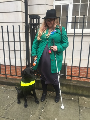 Amy stands next to a guide dog in training. Zena is a black lab cross, she is small and young, she is sat at Amy's feet looking off to the right. Amy holds the lead in one hand and her cane in the other. Amy is wearing a black fedora hat, green coat and grey dress.