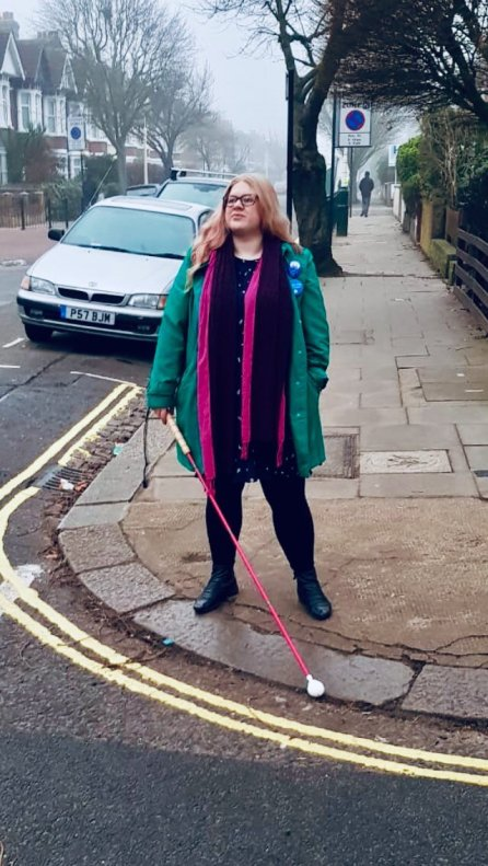 Amy stands on a curb. She holds a pink long cane with a white roller ball tip. She looks out towards the road. She looks confident. Amy wears a green coat and a pink scarf to match her cane.