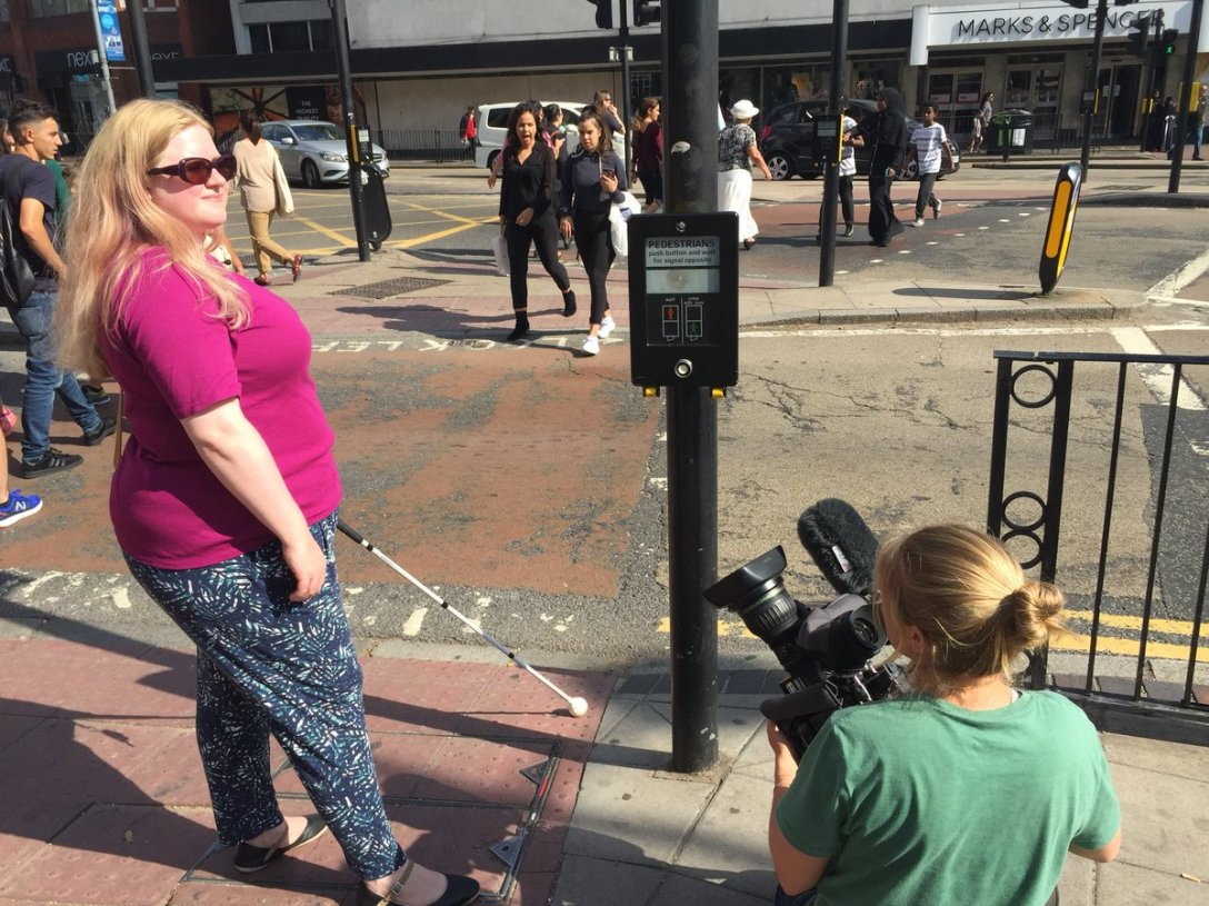 Amy is being filmed. She stands at a pedestrian crossing, her cane in her left hand reaching out onto the tactile paving. In front of her a road, to her right, the pedestrian button box, crouching beside her a camera woman in a green tshirt points the camera up at Amy. Amy wears a pink tshirt, sunglasses, and has tropical pattered trousers.