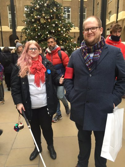 Amy and Other half stand in front of a christmas tree. It's busy and many christmas shoppers are behind them. Amy is wearing a black coat and a red scarf, she holds onto her cane with one hand and onto a Ramble tag with the other. The ramble tag is a guiding device, like a cuff with a handle worn on the upper arm. Other half is wearing the ramble tag, he holds shopping bags, and smiles.