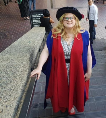 Amy stands half smiling on an outdoor staircase. The photo is taken from above, looking down. Amy wears bright red and purple graduation robes and a flat round PhD cap.