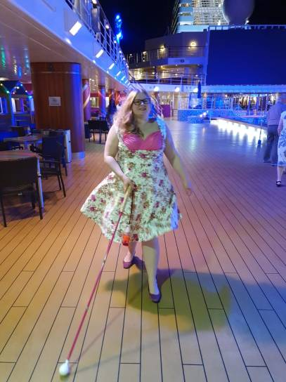 Amy walks along a boat deck at night. She wears a cream and pink floral 50s dress and pink sparkly shoes. She is using her long cane, which is pink with a round roller ball tip.