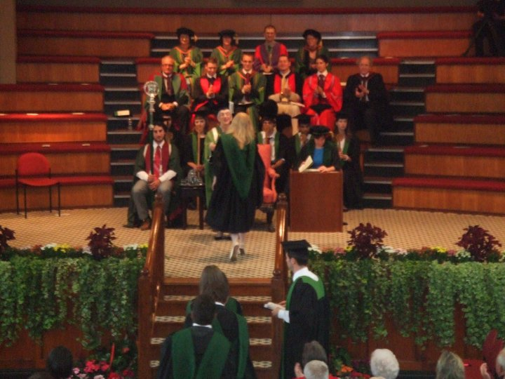 A graduation ceremony. Photographed from a distance, Amy, photographed from behind, has walked up steps and across a stage. In the background on auditorium style seating, a group of academics in robes. Amy's blonde hair is visible, she wears a black academic gown with green hood.