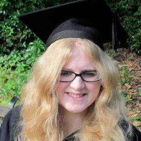 A younger Amy, she loos down with a sad smile, her light blonde hair waving over her face, obscuring some of it. She wears smaller black glasses and a scholars mortar board.