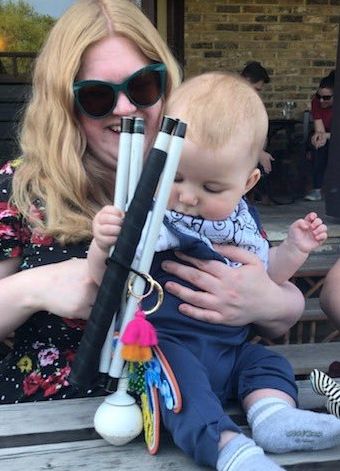 A small baby grabs Amy's folded white cane and lifts it as he looks at it. Amy is holding the baby up as he sits on a picnic table. Amy is smiling and wearing sunglasses.