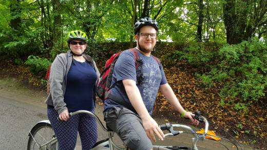 Amy and Other Half are riding a tandem. The photo is taken as they a sit on it, smiling at the camera. The bike is just visible. It has a vintage look with large sweeping upright handles. Behind them a forest.