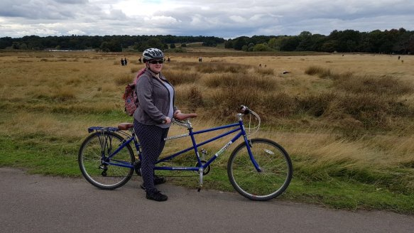 Amy stands astride a tandem in Richmond park, behind her is a vista looking down to a woodland. The bike is lightweight and blue. Amy smiles wearing sunglasses and a helmet.