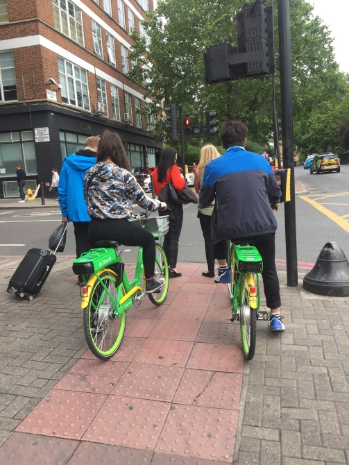 Two people wait on green dockless bikes. They are stopped across the tactile pavement blocking access to the button box.