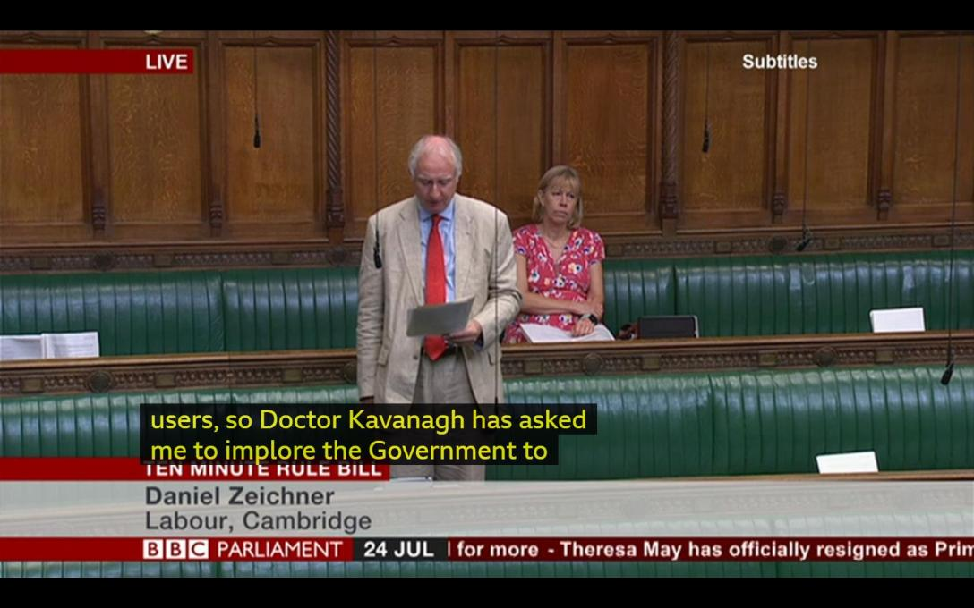 A screenshot of BBC parliament. Daniel Zeichner MP is reading from notes, with a female Mp sat behind him. The subtitles read, so Doctor Kavangh has asked me to implore the government