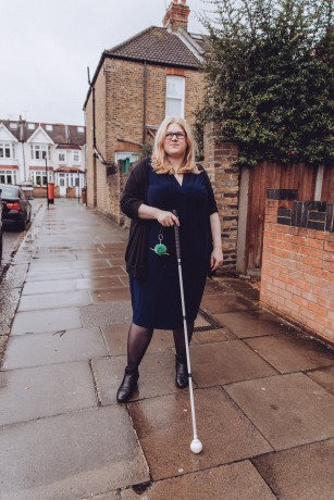 Amy stands in front of her. She wears a dark blue dress, black tights and ankle boots. Amy is looking into the distance with a half smile. She has blonde hair and glasses.