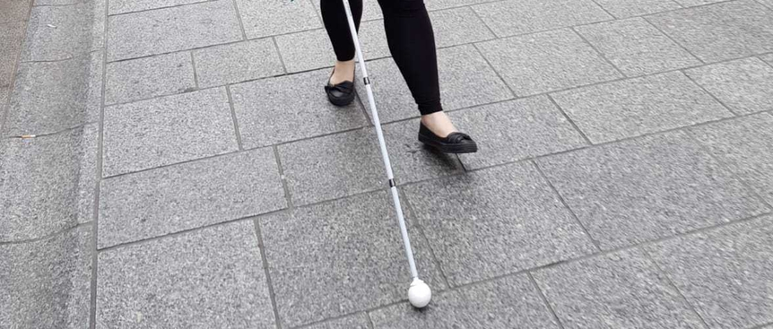 Amy walking down a street using a white cane. Photo is cropped so just her lower legs and white cane show. Amy is mid step, she wears black ballet pumps and leggings.