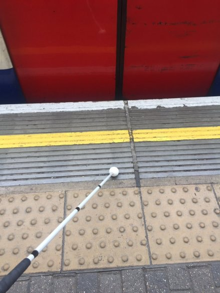 A train platform. The red train doors are closed. A white long cane points out into the photo, the rollerball resting just passed the tactile paving. It points diagonally across towards the yellow line on the platform edge.