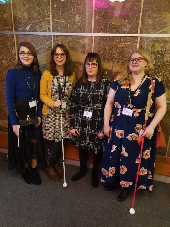 A group of young women stand together. On the far left, Elin, in a blue top and black skirt holding a folded cane. Then Chloe in her trademark mustard yellow cardigan holding her long cane. Then Holly in a black and white dress smiling at the camera. Finally Amy in her blue and floral dress holding her pink long cane.
