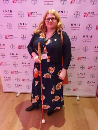 Amy stands in front of a banner with the RNIB logo on it. She wears a long navy dress with big pink flowers on it. She holds a pink long cane, and has a sassy expression.